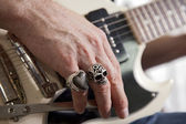 Close-up of mid adult man's fingers with rings playing guitar — Stock Photo
