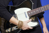 Midsection of young woman holding electric guitar — Stock Photo