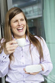 Happy woman holding a cup of coffee and looking away — Stock Photo