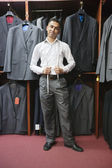 Portrait of young man posing with suits hanging in background — Stock Photo