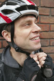 Bicyclist adjusting his helmet — Stockfoto