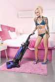 Sexy young tattooed woman in bikini vacuuming bedroom — Stock Photo