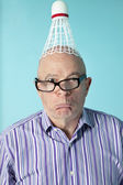 Portrait of senior man making face with shuttlecock on head — Stock Photo
