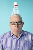 Portrait of angry man with shuttlecock on head over colored background — Stock Photo