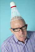 Portrait of angry senior man with shuttlecock on head over colored background — Stock Photo