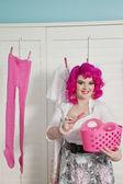 Portrait d'une jeune femme heureuse avec pince à linge suspendre les vêtements dans la chambre — Photo