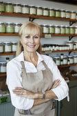 Retrato de un empleado senior feliz con los brazos cruzados en la tienda de especias — Foto de Stock