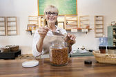 Portrait of a happy female employee pouring spice with scoop in jar — Stock Photo