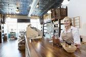 Kupiec stojący szczęśliwy starszych kobiet przyprawa licznik patrząc od hotelu w sklepie — Zdjęcie stockowe