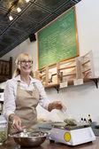 Felice anziano mercante ingrediente sulla scala di peso nel negozio di spezie di misura — Foto Stock