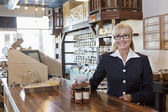 Portrait of a happy female owner standing at counter with spice jar in store — Stock Photo