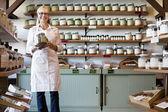 Portrait d'un heureux debout marchand senior avec pot à épices en magasin — Photo