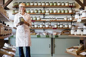 Portrait of a happy senior merchant standing with spice jar in store — Stockfoto