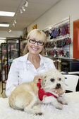 Portrait of senior woman with dog in pet shop — Stock Photo