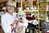 Retrato de una mujer mayor feliz llevando el perro en la tienda de mascotas — Foto de Stock