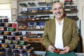 Portrait of a happy mature tobacco shop owner with cans on display — Stock Photo