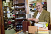 Portrait of a happy owner showing cigar boxes in store — Stock Photo