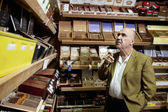 Small tobacco store owner looking at cigar boxes on display in shop — Stock Photo