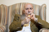 Mature man igniting cigar while sitting on armchair — Stock Photo