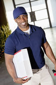 Tilt image of a happy African American delivery man looking at camera — Stock Photo