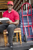Portrait of a happy delivery man sitting on chair with clipboard — Stock Photo