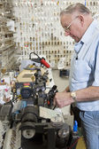Side view of locksmith working in key store — Stock Photo