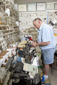 Side view of senior locksmith working in store — Stock Photo