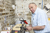 Senior locksmith looking away while making key in store — Stock Photo