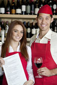 Portrait of young wait staff with wine glass and menu card in bar — Stock Photo