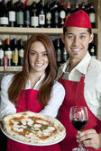 Portrait of a young wait staff with wine glass and pizza — Stock Photo