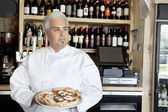 Mid adult chef holding pizza while looking away — Stock Photo