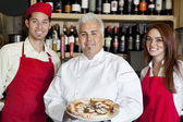 Portrait of a happy chef holding pizza with wait staff — Stock Photo