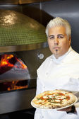 Portrait of a confident mid adult chef holding pizza — Stock Photo
