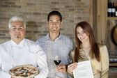 Portrait of mid adult chef holding pizza with young couple — Stock Photo