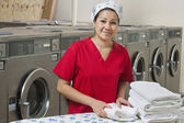 Portrait of a Hispanic female employee with towel in Laundromat — Stock Photo