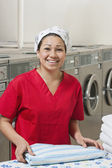 Portrait of a cheerful young woman with towel in Laundromat — Stock Photo