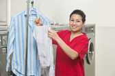 Portrait of a happy young woman with shirt hanging in Laundromat — Stock Photo