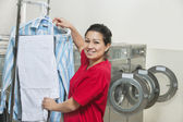 Portrait of a happy young woman drying clothes in Laundromat — Stock Photo