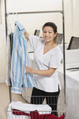 Portrait of a happy young woman hanging shirt in front of washing machines in Laundromat — Stock Photo