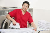 Portrait of a happy woman employee in red uniform ironing clothes in Laundromat — Stock Photo