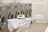 Ironing board with washing machines in Laundromat — Stock Photo