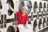 Portrait of a happy young female employee putting clothes in washer — Stock Photo