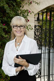 Portrait of a happy senior female agent with clipboard — Stock Photo