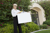 Portrait of a happy senior female agent hammering sign board in lawn — Stock Photo
