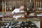 Mature gun shop owner looking at rifle in store — Stock Photo