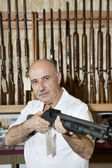 Mature gun merchant with rifle looking away — Stock Photo