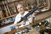 Portrait of a happy mature merchant with rifle in gun shop — Stock Photo
