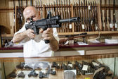 Mature merchant aiming with rifle in gun shop — Stock Photo
