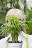 Close-up of a pot plant in front of senior woman's face — ストック写真
