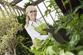 Portrait of a happy senior gardener cultivating plants in greenhouse — Stock Photo